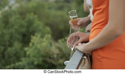 Girls with glasses of champagne stand on the terrace