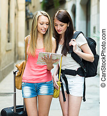 Girls with luggage reading map - Two young girls with...