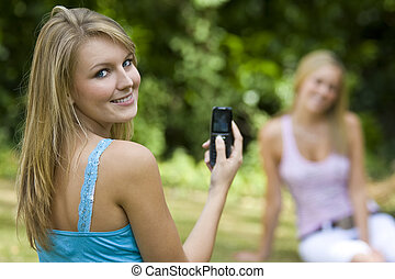 A beautiful young blond woman taking a picture of her friend on her mobile phone