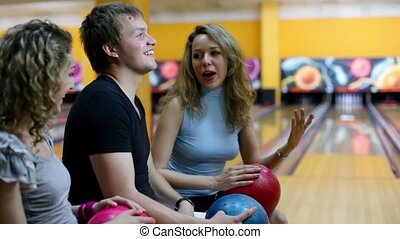 girls with one guy talk and smile at background of bowling lane