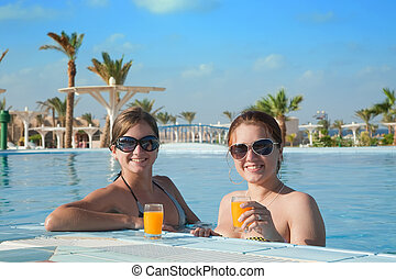 Girls with orange juice at resort hotel