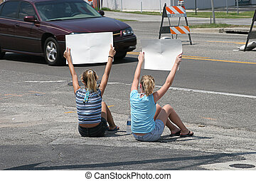 Girls With Signs - Two teenaged girls holding signs for...
