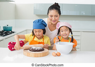 Girls with their mother preparing cookies in kitchen