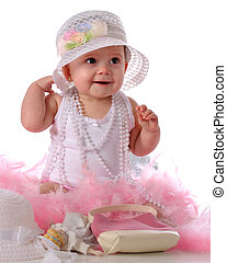Girly Girl - A happy baby girl wearing beads, a fancy hat, ...