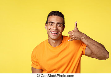 Give me call babe. Sexy confident young handsome man making phone gesture near head and smiling excited, look upbeat and assertive, asking contact him as trying flirt, stand yellow background