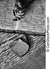 Praying hands on a bible with bread