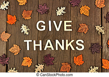 Give Thanks wooden letters and autumn leaves over rustic wood