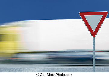 Give way yield traffic sign and moving truck