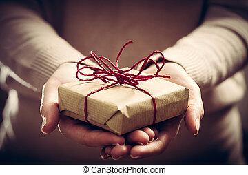 Giving a gift, handmade present wrapped in paper. Christmas...
