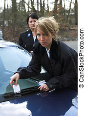 Giving a ticket - Female police officer putting a parking...