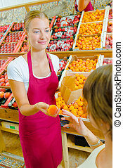 Giving an orange to a customer