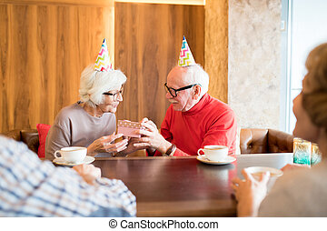 Giving gift to birthday senior woman