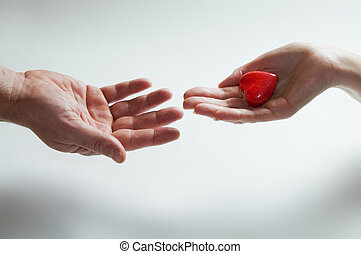 Giving heart love concept. One hand gives symbolic heart to...