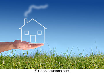 Hand giving new house. Green grass and blue sky on the background.