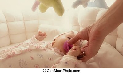 Giving pacifier to fussy baby in the cot - Newborn baby girl...