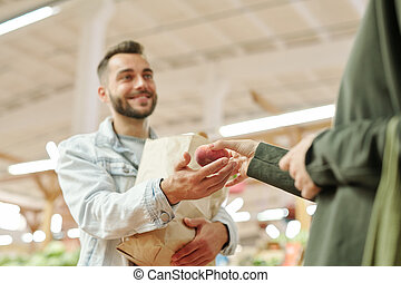 Giving peach to husband at market