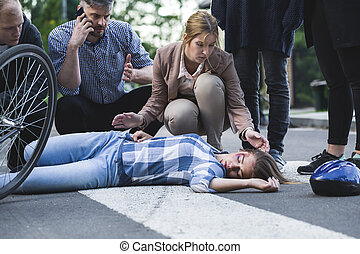 Man calling the emergency and woman bending over the accident casualty