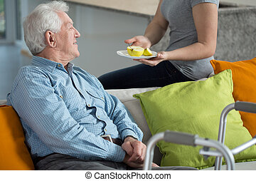Young female caregiver giving the fruit to older man