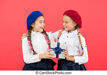 Giving the gift for you. Cute small child giving a present to friend on pink background. Adorable little girl enjoy giving the gift to schoolmate. Giving and receiving go together