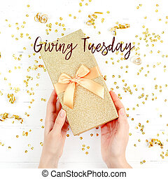 Giving Tuesday concept with golden box in hands - Giving ...