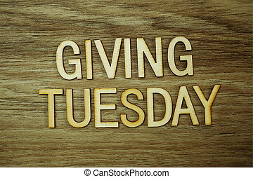 Giving Tuesday text message on wooden background