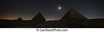 Giza pyramids light up during sound and light show to celebrate Ramadan Feast festival in Cairo, Egypt. The pyramids of Cheops and Chephren and mykerin under the night starry sky and the moon.
