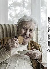 glücklich, ältere frau, essende, kekse