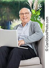 glücklich, älterer mann, sitzen, mit, laptop, auf, couch