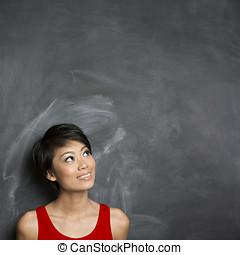 glücklich, asiatische frau, stehende , vor, a, leer, chalkboard.