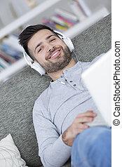 glücklich, entspanntes, junger mann, hören musik, hause