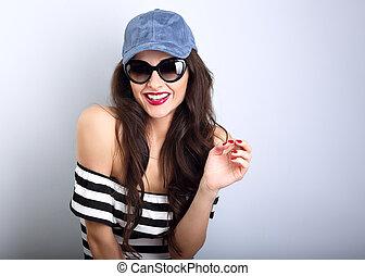 glücklich, genuß, junge frau, in, sonne brille, blau, baseballmütze, posierend, und, innen schauen, gestreift, blouse., closeup, porträt