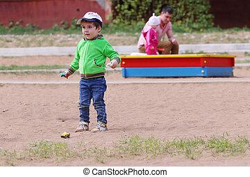glücklich, hübsch, kleiner junge, spiele, mit, kinderauto, auf, kinder, spielplatz, an, sommer, zwei leute, fokus