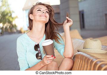 glücklich, hübsches mädchen, mit, bohnenkaffee, sitzen, auf, der, stuhl