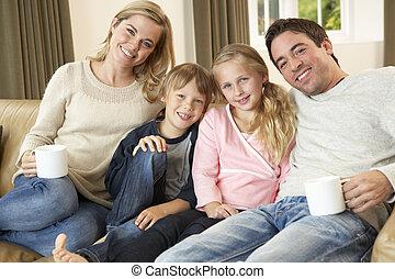 glücklich, junge familie, sitzen sofa, halten bechern