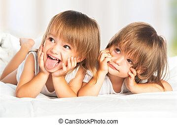 glücklich, kleine m�dchen, zwillinge, schwester, bett, unter, der, decke, spaß haben, lächeln
