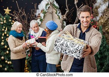glücklich, mann, angebot, weihnachtsgeschenk, mit, familie hintergrund