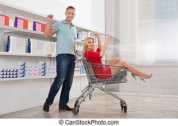 glücklich, mann- zujubeln, mit, frau sitzen, in, einkaufswagen