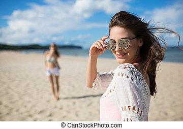glücklich, schöne frau, in, sonnenbrille, stehende , auf, sandstrand, mit, freund
