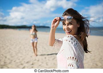 glücklich, schöne frau, stehende , auf, sandstrand, mit, freund, lachender