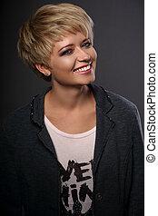 glücklich, toothy, lächeln, junger, blond, frau, mit, kurz, bob, haar- art, innen schauen, grau, poppig, jacke, auf, dunkel, hintergrund., closeup, porträt