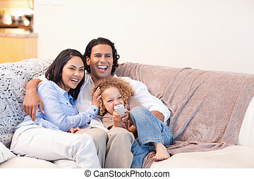 glückliche familie, aufpassendes fernsehen, zusammen