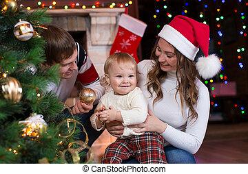 glückliche familie, kind, dekorieren weihnachtsbaum, vor, kaminofen, in, wohnzimmer