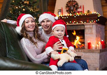 glückliche familie, sitzen sofa, bei, weihnachtsbaum, und, kaminofen, in, wohnzimmer