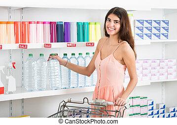 glückliche frau, kaufen, flasche, von, tafelwasser, in, supermarkt