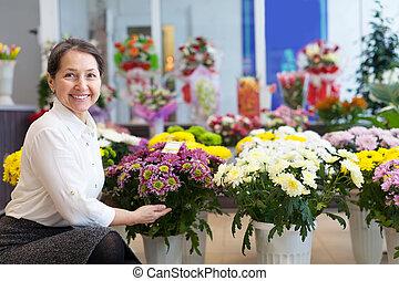 glückliche frau, mit, crysantheme, an, kaufmannsladen