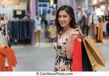 glückliche frau, mit, einkaufstüten, in, kleidung- speicher
