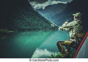 Glacial Lake Fly Fishing. Caucasian Fisherman on a Lake...