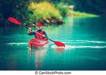 Glacial Lake Kayak Trip. Caucasian Tourist Paddling in the...