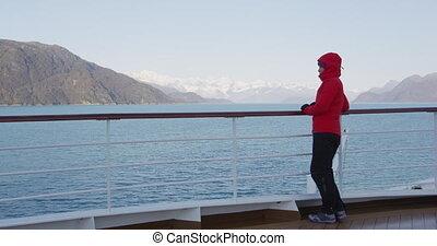Glacier Bay Alaska cruise ship passenger looking at Alaskan mountains exploring Glacier Bay National Park, USA. Woman on travel sailing Inside Passage enjoying view of Johns Hopkins Glacier.