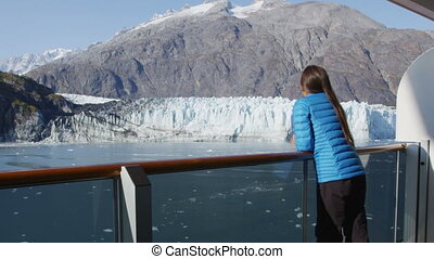 Glacier Bay Alaska cruise ship passenger looking at glacier in Glacier Bay National Park, USA. Woman on travel sailing Inside Passage enjoying luxury stateroom balcony with view of Margerie Glacier.